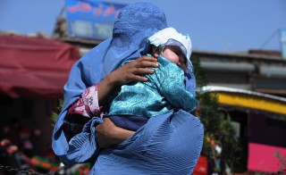 An Afghan woman carries her child in Herat on Aug. 14, 2013. Photo by Aref Karimi/AFP/Getty Images