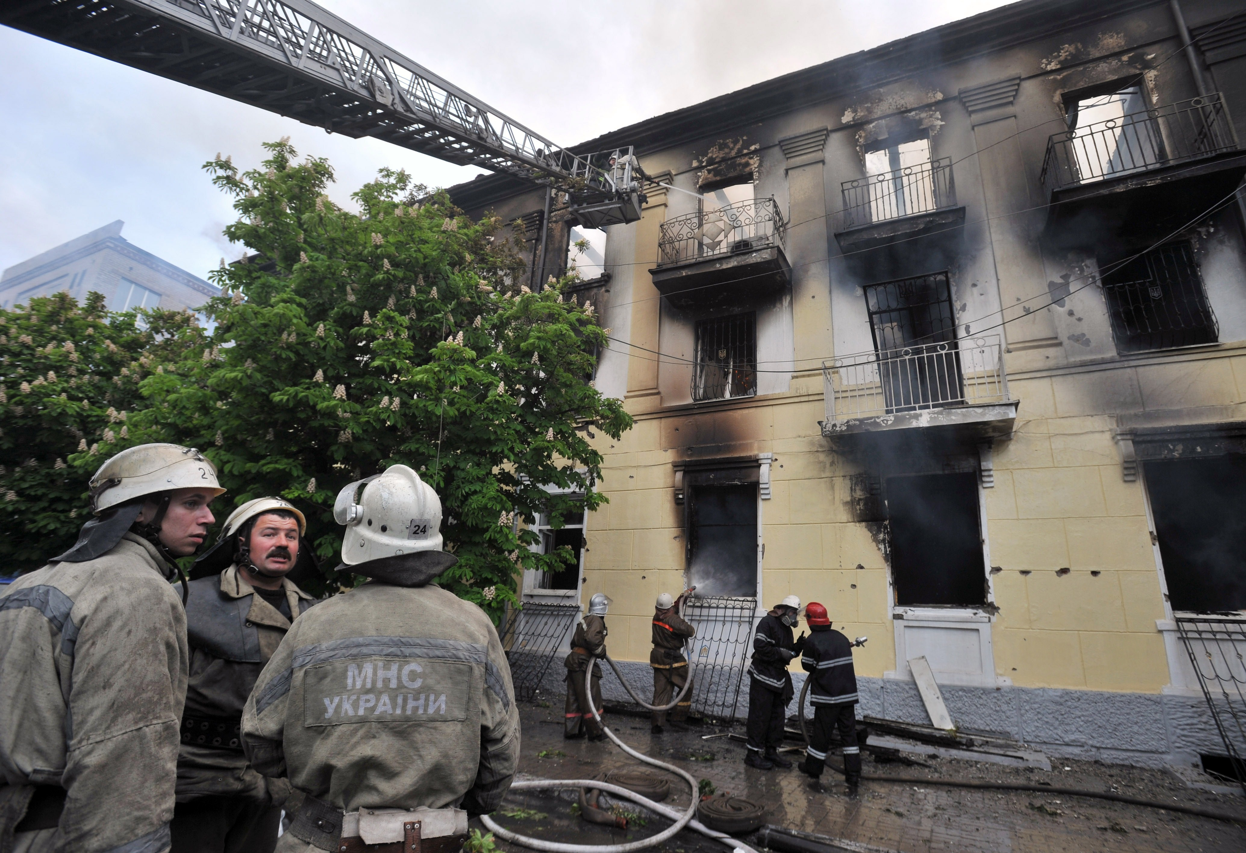 Firefighters extinguish a fire that erupted in a building following fierce fighting in the southeastern Ukrainian city of Mariupol on May 9, 2014. Fierce fighting between Ukrainian troops and pro-Russian rebels broke out in Mariupol, killing at least 21 people, all but one of them insurgents, according to the interior minister. Photo by Genya Savilov/AFP/Getty Images