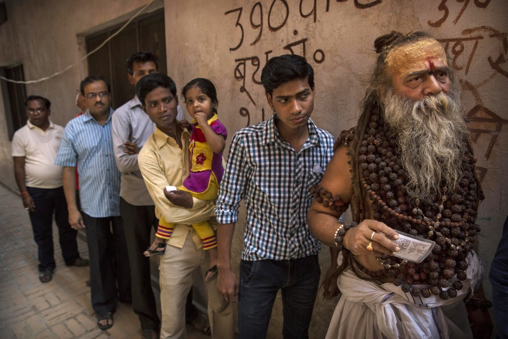 A Hindu holy man holds his election card as he waits in line to vote with others at a polling station in Varanasi, India Monday. Photo by Kevin Frayer/Getty Images