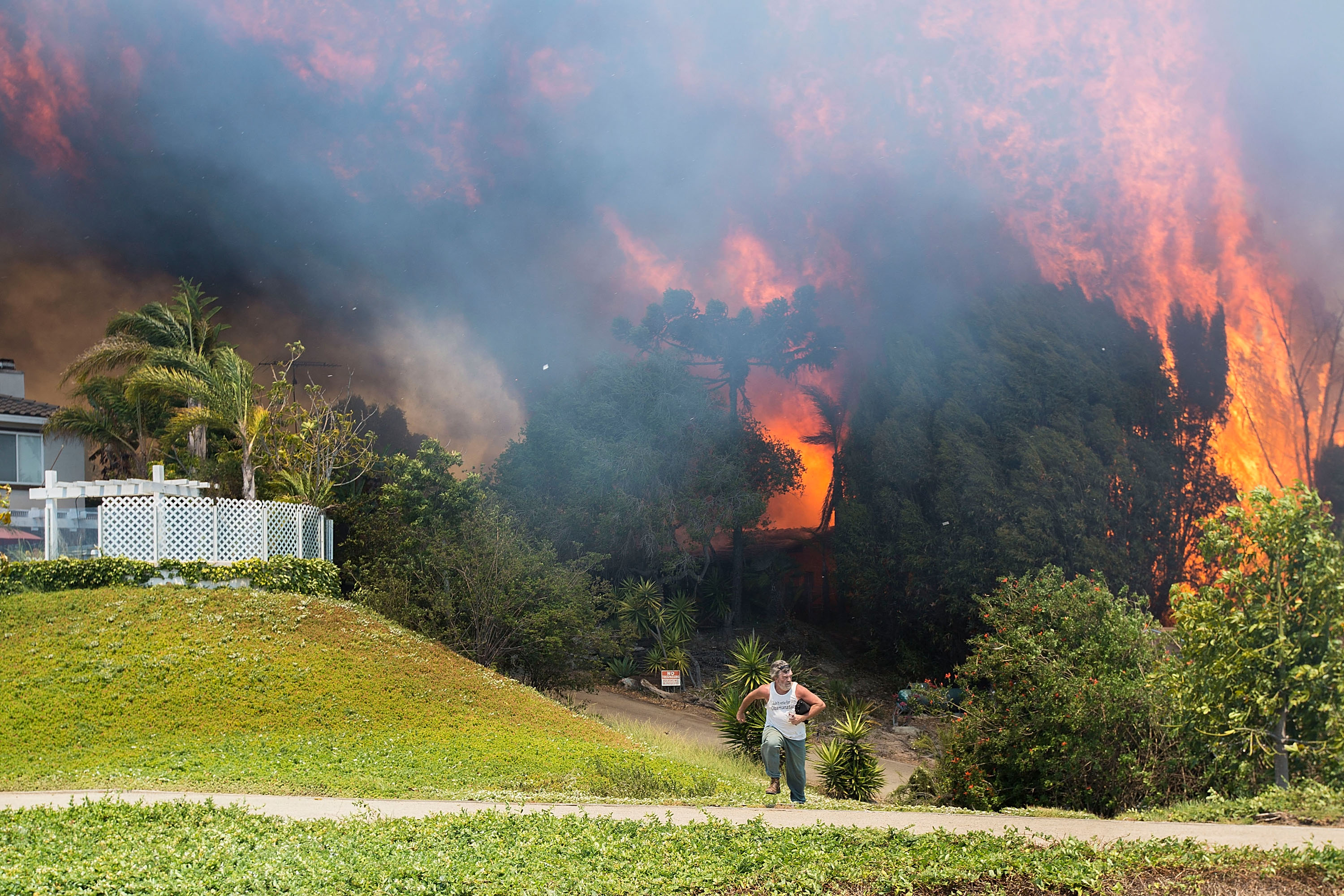 CARLSBAD, CA - MAY 14: A man flees erupting flames as a house on Skimmer Court is engulfed by the Poinsettia Fire on May 14, 2014 in Carlsbad, California. Thirty homes have burned in the fast-moving Carlsbad blaze, fueled by record heat, high winds and dry conditions. At least four other fires advanced in nearby communities. (Photo by Daniel Knighton/Getty Images)
