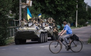 A man rides a bicycle past armored vehicles holding Ukrainian army soldiers in the eastern Ukrainian town of Volnovakha on May 22, 2014. Photo by Dimitar Dilkoff/AFP/Getty Images