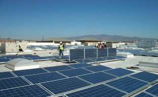 Workers install solar panels on top of a Walmart in Chula Vista, California. Photo by Walmart/Flickr