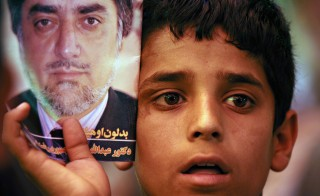 An Afghan boy holds a photo of presidential candidate Abdullah Abdullah during a campaign event in Istalif district of Kabul on Aug. 9, 2009. Photo by Massoud Hossaini/AFP/Getty Images