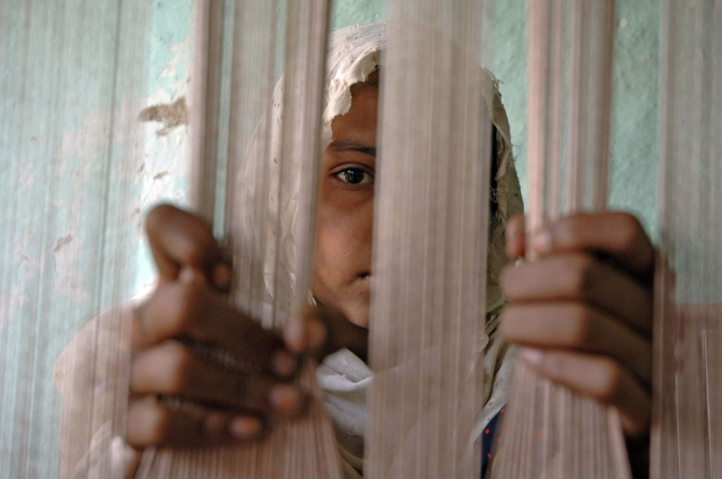 Young girl works as a child weaver in  the district of Lahore. Photo by International Labour Organization, courtesy of Flickr.