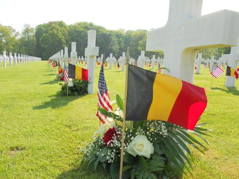 Flags and flowers were placed at a headstone at Ardennes American Cemetery in Belgium for Memorial Day in 2013. The WWII cemetery has 5,323 American casualties buried there, and another 462 missing in action memorialized by name. Photo: ABMC