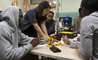 Nicole Bell, a science teacher at Coolidge High School in Washington, D.C., works with robotics club members Teresa Buckner, 16, and Roshawn Canns, 17, May 1, 2014. Photo by PBS NewsHour