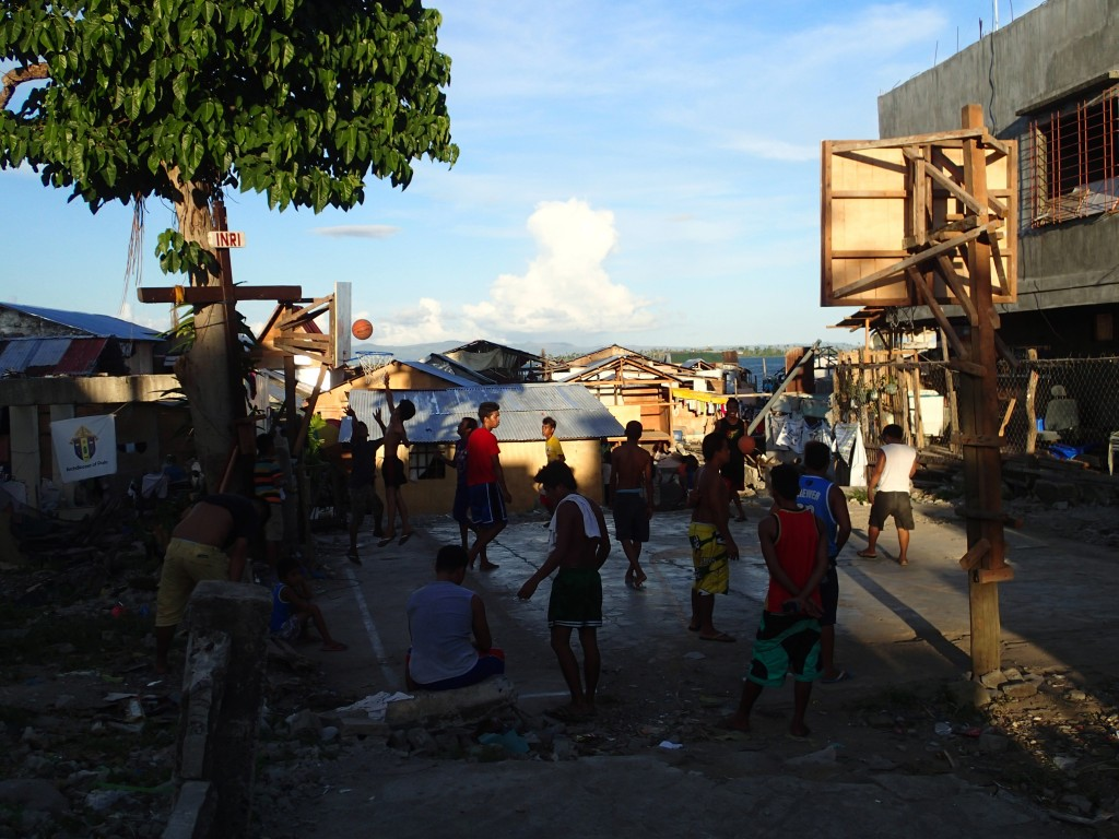 A basketball game in the midst of shelters built out of scrap metal and wood. Thousand live in neighborhoods like this that have popped up since the typhoon. Basketball is a national obsession.