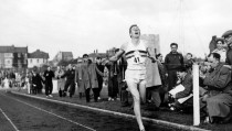 Athletics Oxfordshire, England. 6th May, 1954. Roger Bannister breaks the tape as he crosses the winning line to complete the historic four minute mile record.
