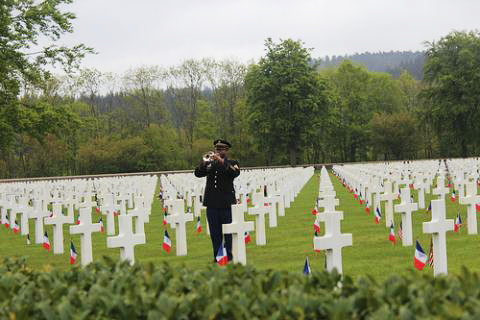 A bugler stands among the headstones at Epinal American Cemetery in France during the 2013 Memorial Day ceremony. The WWII cemetery holds the remains of 5,255 Americans and memorializes another 424 missing in action by name. Photo: ABMC