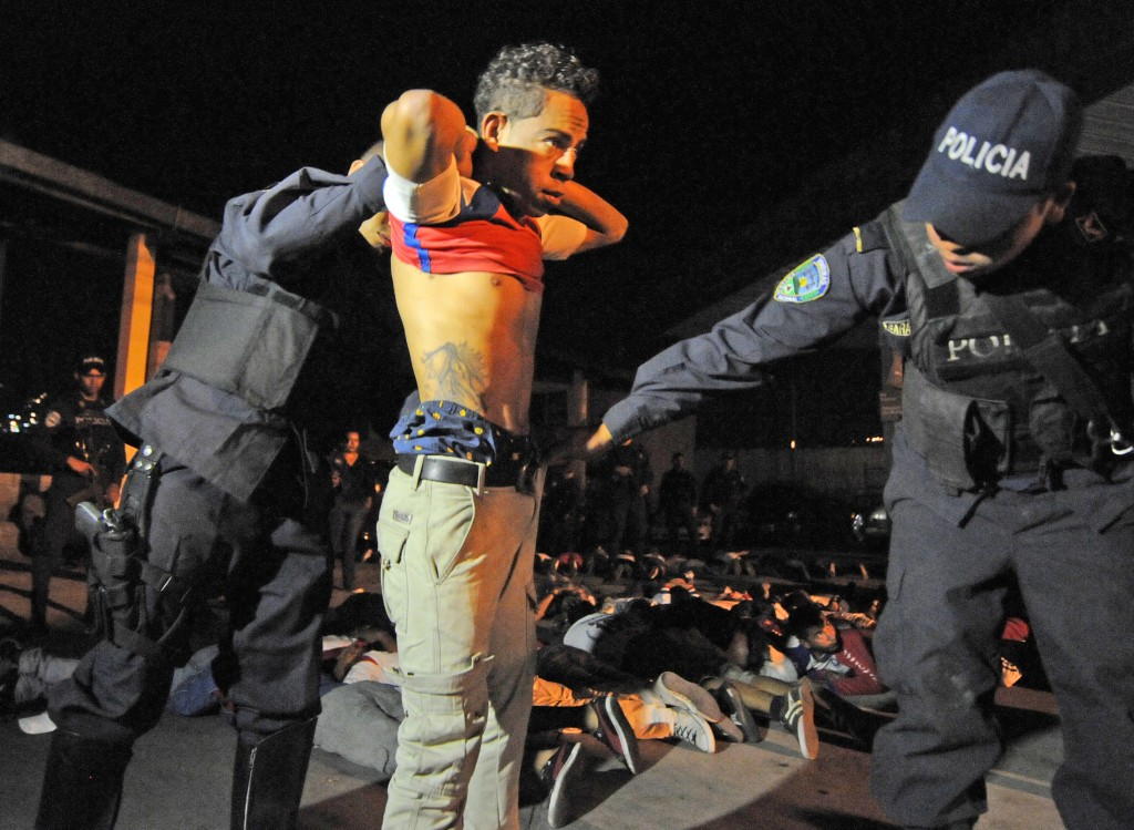 "Honduran policemen frisk a young man belonging to the Olympia club's Ultrafiel fans group, notoriously infiltrated by the ""maras"" (juvenile gangs), in Tegucigalpa, on February 10, 2013. Photo by Orlando Sierra/AFP/Getty Images"