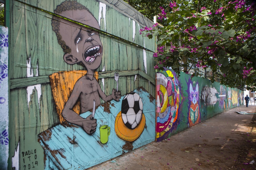 Brazilian street artist Paulo Ito drew a picture of a crying child, who is served a soccer ball to appease his hunger, on the wall of a public school in Sao Paulo, as Brazil readies for the 2014 World Cup. Photo by Miguel Tovar/LatinContent/Getty Images