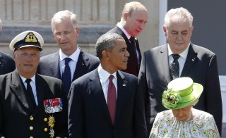 Russian President Vladimir Putin passes behind President Barack Obama as he arrives for a group photo for the 70th anniversary of the D-Day landings at Benouville Castle, June 6, 2014. AFP PHOTO / POOL / Regis Duvignau