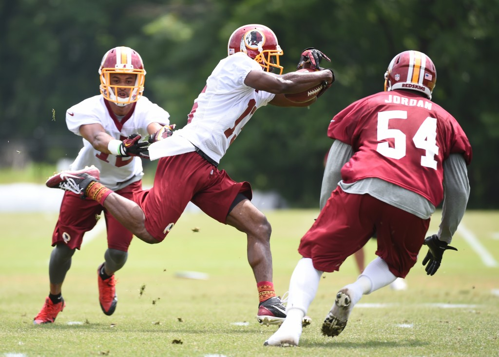 Washington Redskins' Aldrick Robinson (No. 15) speeds past Lee Doss (No. 18) and Akeem Jordan (No. 54) during their final round of organized team activities on June 11 in Ashburn, Va. Photo by Jonathan Newton/The Washington Post via Getty Images