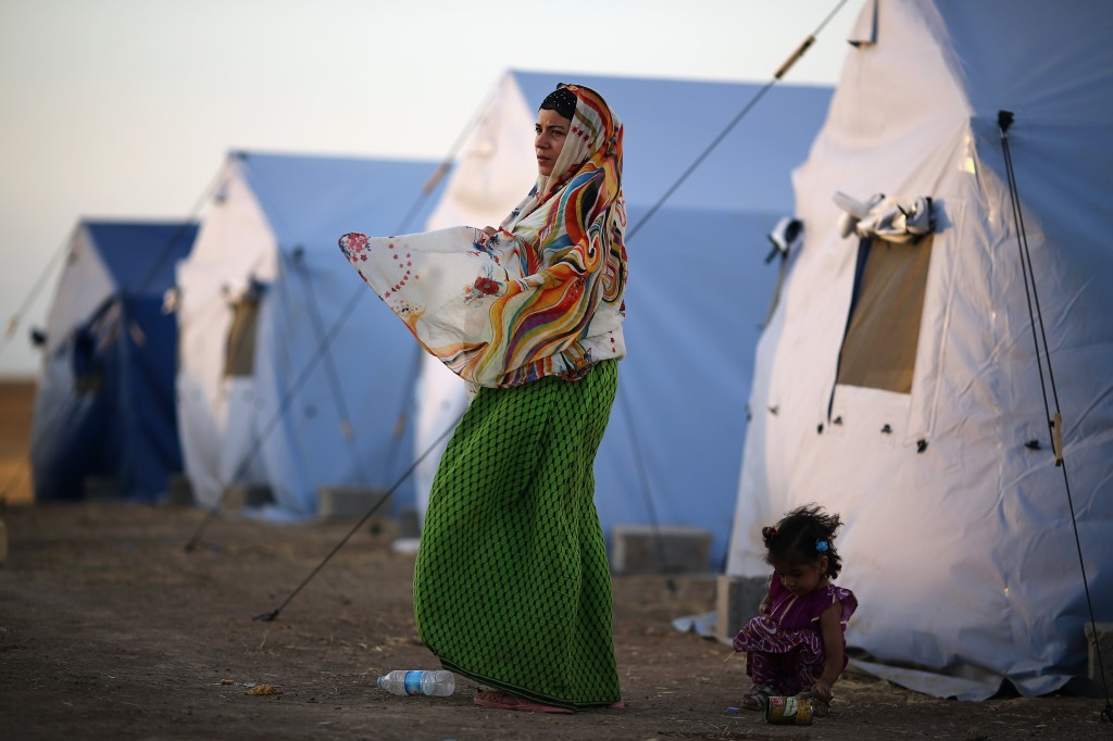 A woman stands outside a tent at a temporary displacement camp set up next to a Kurdish checkpoint on June 13 in Kalak, Iraq. Photo by Dan Kitwood/Getty Images