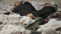 Detainees sleep in a holding cell at a U.S. Customs and Border Protection processing facility, on June 18, 2014, in Brownsville,Texas. Thousands of unaccompanied children have entered the country illegally since 2012. Photo by Eric Gay-Pool/Getty Images