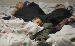 Detainees sleep in a holding cell at a U.S. Customs and Border Protection processing facility, on June 18, 2014, in Brownsville,Texas. Thousands of unaccompanied children have entered the country illegally since 2012. A Senate probe faulted the Health and Human Services Department  on Thursday for its failure to conduct the most basic checks, like background checks and home visits, on the adults entrusted with caring for the children. Photo by Eric Gay-Pool/Getty Images