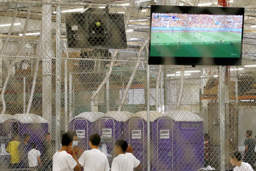 Detainees watch a World Cup soccer match from a holding cell where hundreds of mostly Central American immigrant children are being processed and held at the U.S. Customs and Border Protection Nogales Placement Center on June 18, 2014, in Nogales, Ariz. Photo by Ross D. Franklin-Pool/Getty Images