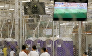 Detainees watch a World Cup soccer match from a holding cell where hundreds of mostly Central American immigrant children are being processed and held at the U.S. Customs and Border Protection Nogales Placement Center on June 18, 2014, in Nogales, Arizona. Photo by Ross D. Franklin-Pool/Getty Images