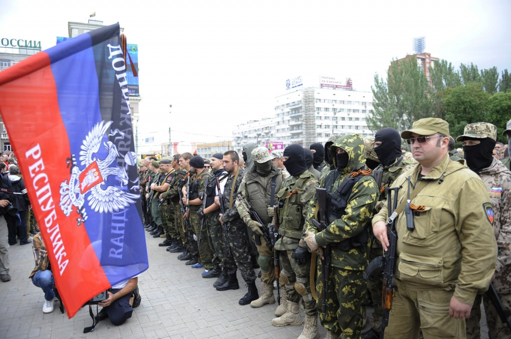 "A flag of the so-called People's Republik of Donetsk waves as pro-Russian militants take the military oath during the ceremony in the centre of the eastern Ukrainian city of Donetsk on June 21, 2014. Russian President Vladimir Putin has ordered troops in central Russia on ""full combat alert,"" the defence minister said on Saturday, a day after the Kremlin confirmed it was beefing up its military presence at the border with Ukraine. AFP PHOTO/ ALEXANDER KHUDOTEPLY        (Photo credit should read Alexander KHUDOTEPLY/AFP/Getty Images)"
