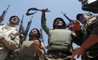 Iraqi troops raise up their weapons as they arrive to support the Sunni anti-Al-Qaeda militia Sahwa (Awakening) in its fight against anti-government militants, including from the jihadist Islamic State of Iraq and the Levant (ISIL) in the Anbar province on June 21, 2014 in the city of Ramadi, west of the capital Baghdad. Photo by AFP/Getty Images