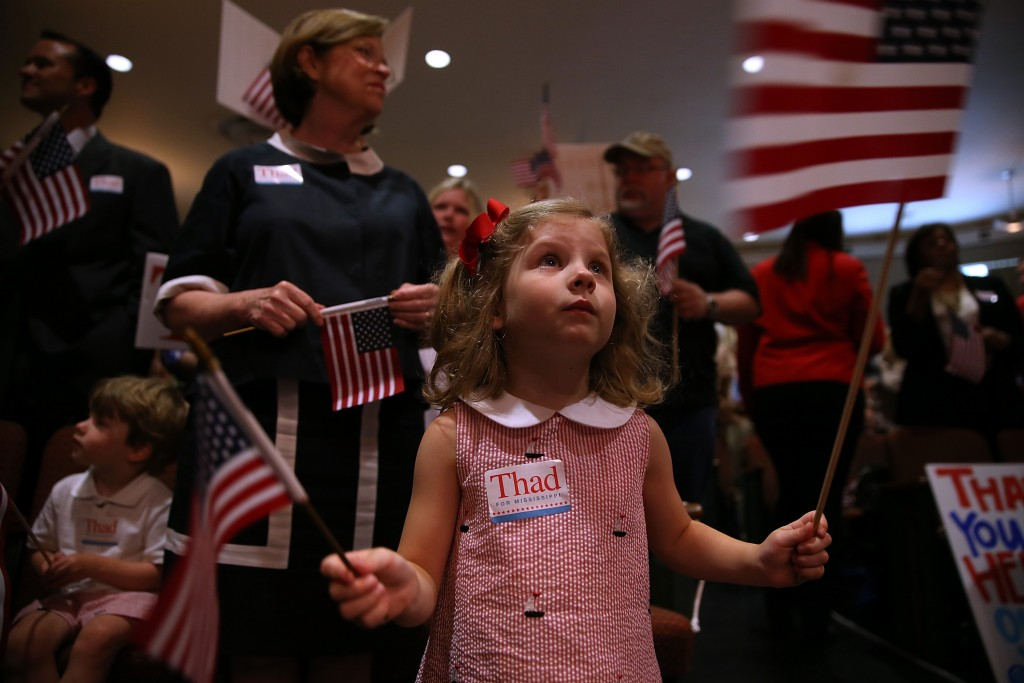 A young supporter of Sen. Thad Cochran waves American flags during a campaign rally at the Mississippi War Memorial Building Monday in Jackson. Photo by Justin Sullivan/Getty Images