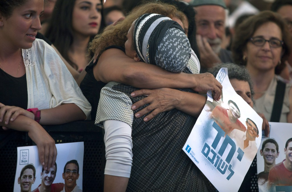 A woman hugs Iris Yifrah, mother of missing Israeli teen Eyal Yifrah, during a rally in support of three missing Israeli teenagers on June 29 in Tel Aviv, Israel. Photo by Lior Mizrahi/Getty Images
