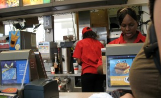 Seattle's lowest wage workers are getting a raise. The city council on Monday approved a measure that would raise the minimum wage to $15 per hour by 2021. Photo of a McDonald's worker by Flickr user Consumerist Dot Com