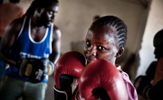 At 13, Tabitha Njeri will lead the 'Life Skills' classes after training has finished. Amongst many things, 'Life Skills' involve confidence building, sexual health education and gender role debates. Priest, her boxing teacher, mentor and trainer spars in the background. Photo by Mia Collis