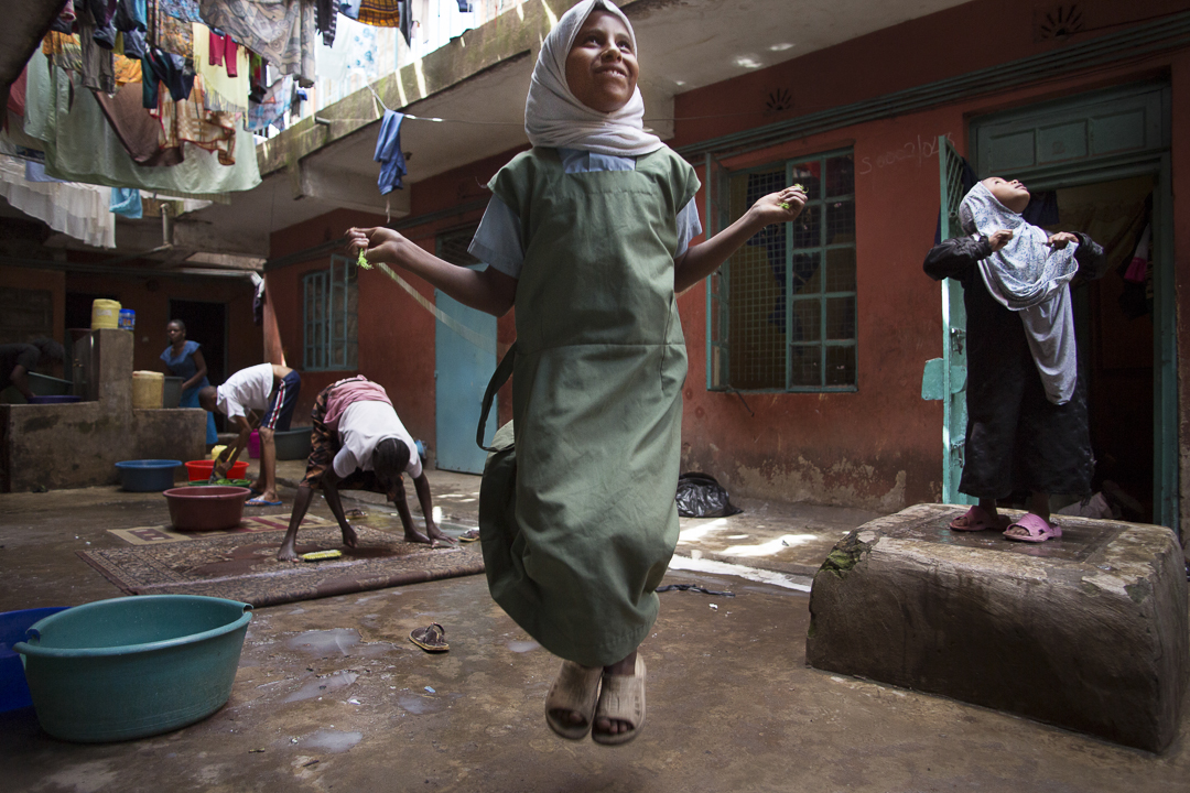 A refugee girl jumps rope in her apartment complex courtyard in Nairobi, Kenya, where it is safer to play than out on the street. Photo by Amy Toensing