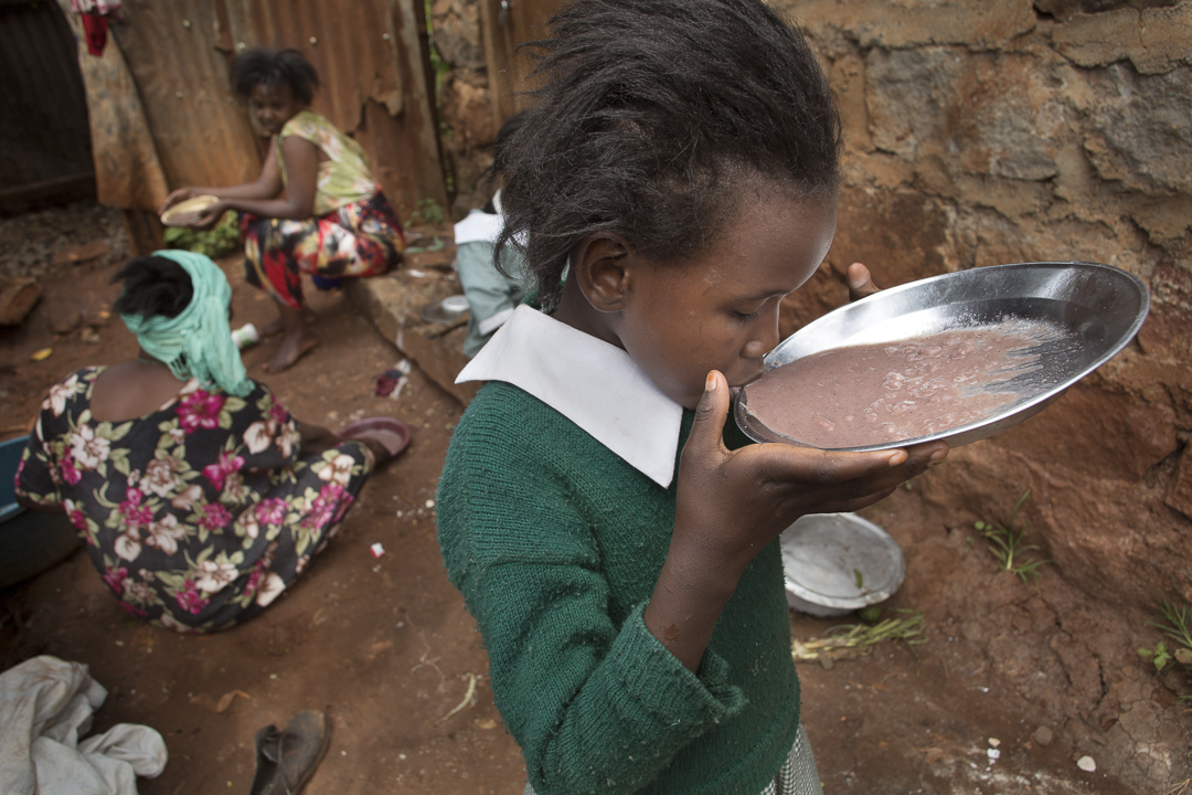 A girl sips porridge in Nairobi, Kenya. In urban areas, getting food is a challenge particularly for refugee families. Photo by Amy Toensing