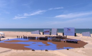 Dancers march across a stage representing the world in the celebration of D-Day. Image from D-Day celebration video