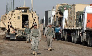 US soldiers walk past military vehicles at Camp Victory on the outskirts of the Iraqi capital Baghdad in November 2011. Photo by Ahmad Al-Rubaye/AFP/Getty Images