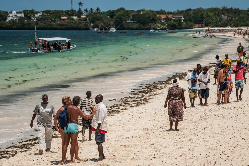Tourists interact with local vendors on the beach in Malindi, Kenya. Photo by Mia Collis/PBS NewsHour