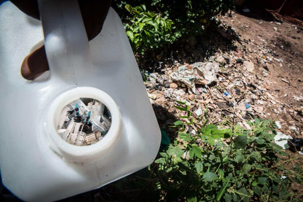 Used needles are collected  from the ground by The Omari Project's outreach workers at a heroin den in Malindi. Photo by Mia Collis/PBS NewsHour