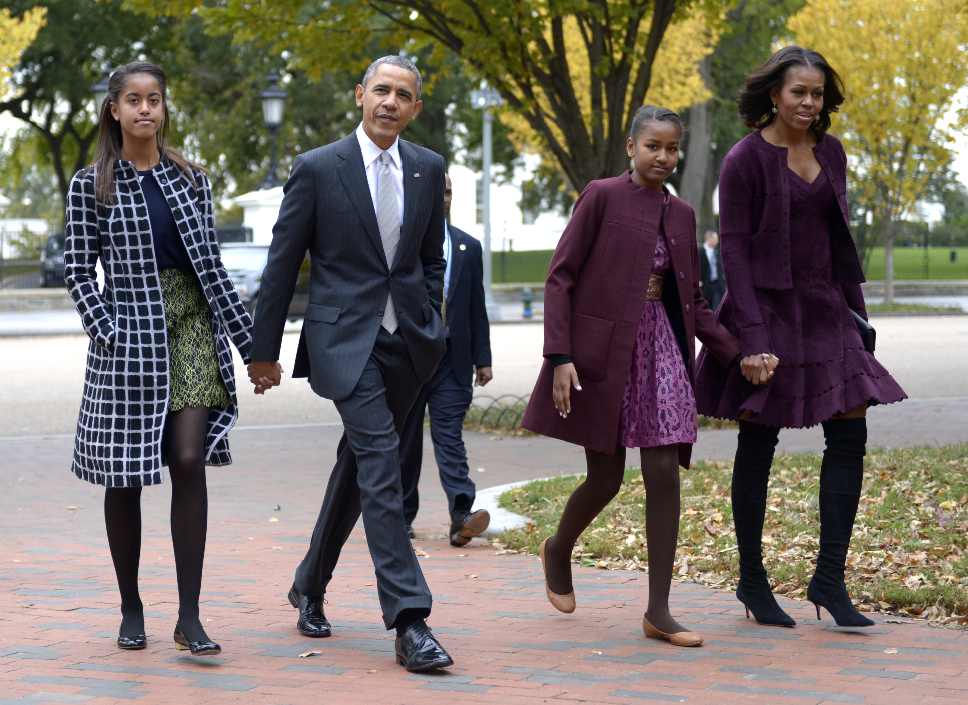President Barack Obama walks with his wife Michelle Obama (R) and two daughters Malia Obama (L) and Sasha Obama (2R) through Lafayette Park to St John's Church to attend service October 27, 2013 in Washington, DC. Photo by Shawn Thew-Pool/Getty Images