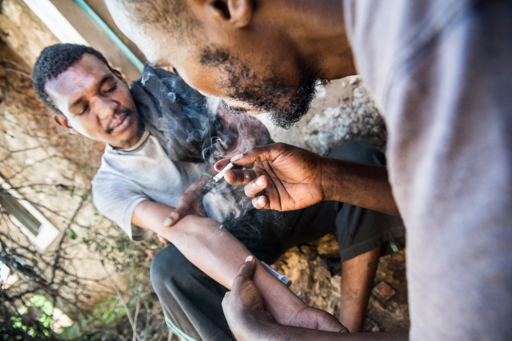 Shee Omar shoots up while Ahmed Mohamed smokes a joint filled with heroin and marijuana in a back alley of Malindi. Photo by Mia Collis/PBS NewsHour