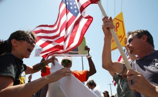 A protester who opposes arrivals of buses carrying  undocumented migrants for processing at the Murrieta Border Patrol Station and a counter-demonstrator (L) face off on July 4 in Murrieta, California. Photo by David McNew/Getty Images