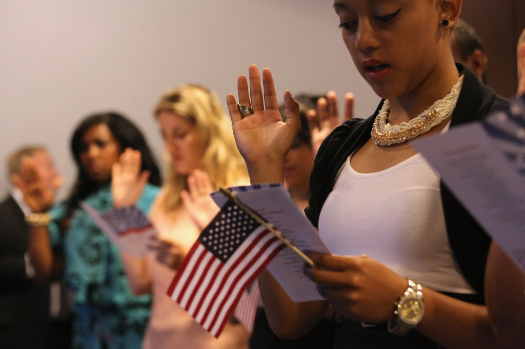 Caption:NEW YORK, NY - JULY 09: Immigrants take the oath of allegiance to the United States during a naturalization ceremony on July 9, 2014 in New York City. Seventy-five people became American citizens at a event held by U.S. Citizenship and Immigration Services (USCIS), at the League of United Latin American Citizens (LULAC), convention in midtown Manhattan. (Photo by John Moore/Getty Images)   Photo by John Moore/Getty Images