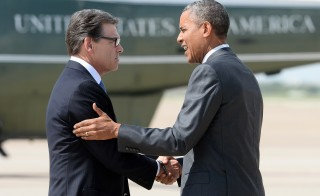 President Obama is greeted by Texas Gov. Rick Perry as he arrives in Dallas, Texas Wednesday for a meeting with local elected officials and faith leaders to discuss the humanitarian situation at the Southwest border. Photo by JEWEL SAMAD/AFP/Getty Images