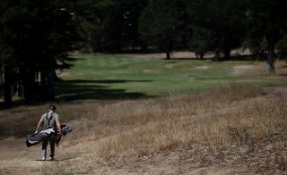 A golfer walks past dead grass on a fairway at Gleneagles Golf Course in San Francisco, California, on July 11. Photo by Justin Sullivan/Getty Images