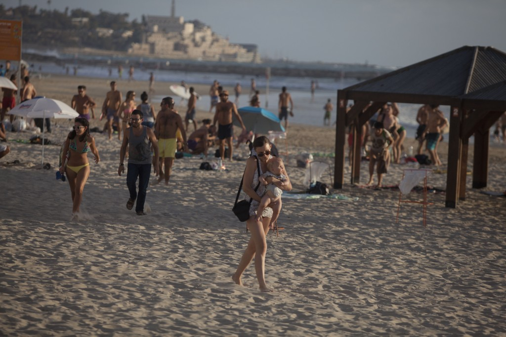 People leave a beach in Tel Aviv, Israel, after hearing a rocket siren on July 15. Photo by Lior Mizrahi/Getty Images