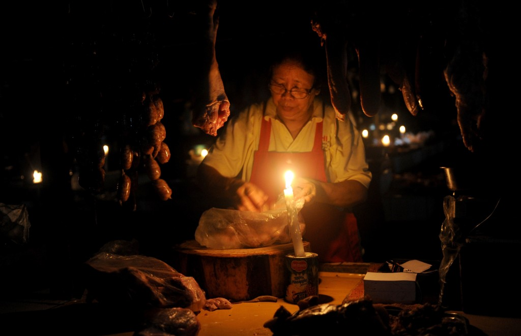 A vendor sells meat by candle light in Manila on July 17, 2014. Millions of people in the Philippines endured a second sweltering day without power on July 17 after a ferocious typhoon paralysed the capital and wrecked flimsy rural homes.    Photo by  Jay Directo/AFP/Getty Images
