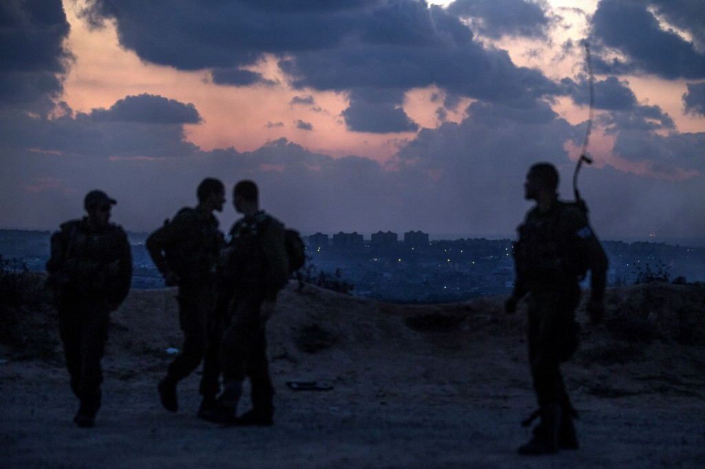 Israeli soldiers stand near the southern Israeli border with the Gaza Strip. Israeli air strikes in Gaza killed four children today, medics said, after a humanitarian lull in a 10-day conflict that has killed 237 Palestinians. Photo by Jack Guez/AFP/Getty Images