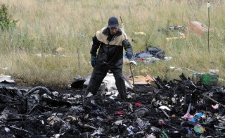 A rescue worker uses sticks to mark the location where bodies of victims have been found at the site of the crash of a Malaysian airliner carrying 298 people from Amsterdam to Kuala Lumpur in Grabove, in rebel-held east Ukraine, on Friday. President Barack Obama and members of the U.N. Security Council demanded a full, independent investigation into the apparent shooting down of the Malaysia Airlines jet. Photo by Dominique Faget/AFP/Getty Images