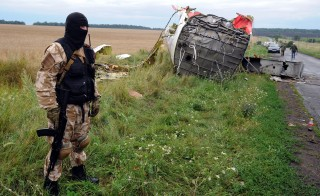 An armed pro-Russia militant stands guard at the site of the crash of a Malaysian airliner carrying 298 people from Amsterdam to Kuala Lumpur in Grabove, in rebel-held east Ukraine. U.S. Secretary of State John Kerry said in a round of interviews Sunday that there is a very clear sign of responsibility pointing to the rebels for this tragedy. Photo by Dominique Faget/AFP/Getty Images