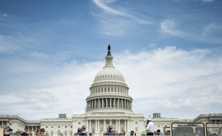 Tourists pass the US Capitol building on a tour bus July 19, 2014 in Washington, DC. Congress has been on break for the month of August. (Photo: BRENDAN SMIALOWSKI/AFP/Getty Images)