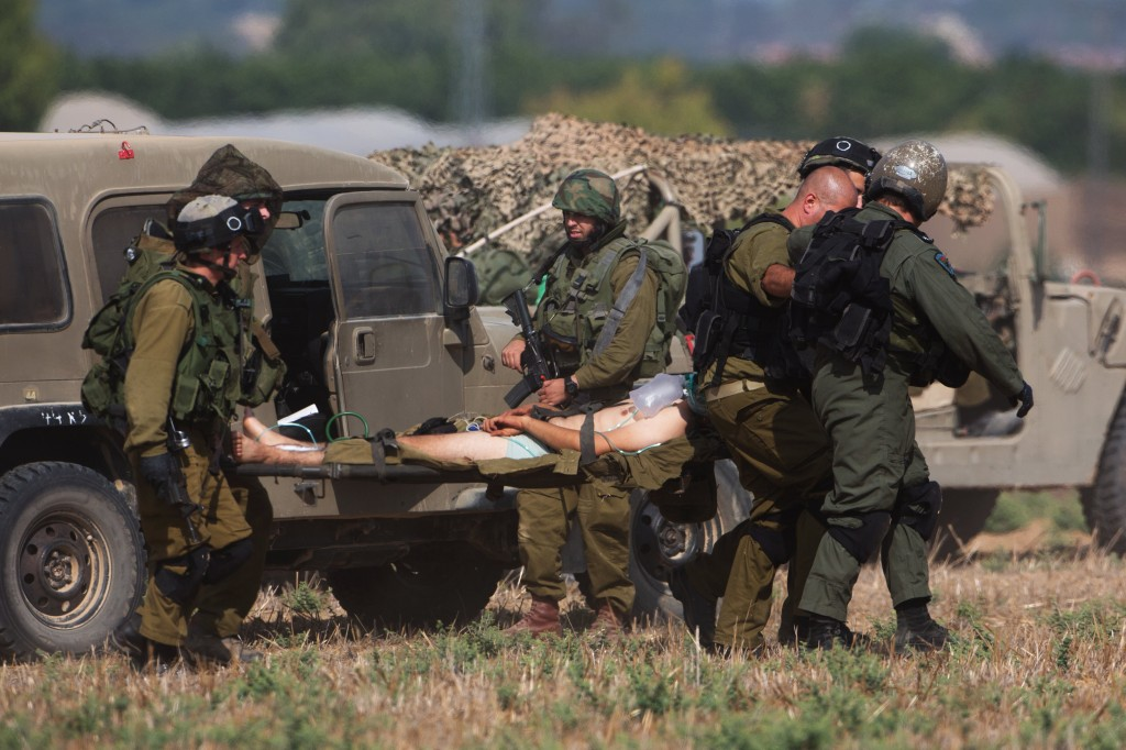 An injured Israeli soldier is evacuated from near the Israeli border with Gaza Strip on July 21, 2014, following heavy fights between Israeli soldiers to Palestinian militants. Photo by Menahem Kahana/AFP/Getty Images