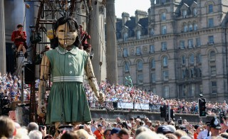 Crowds watch the The Little Giant Girl, one of the giant Royal De Luxe street puppets taking part in Liverpool's World War I centenary commemorations, walks through the streets of Liverpool on July 25, 2014 in Liverpool, England. Photo by Christopher Furlong/Getty Images