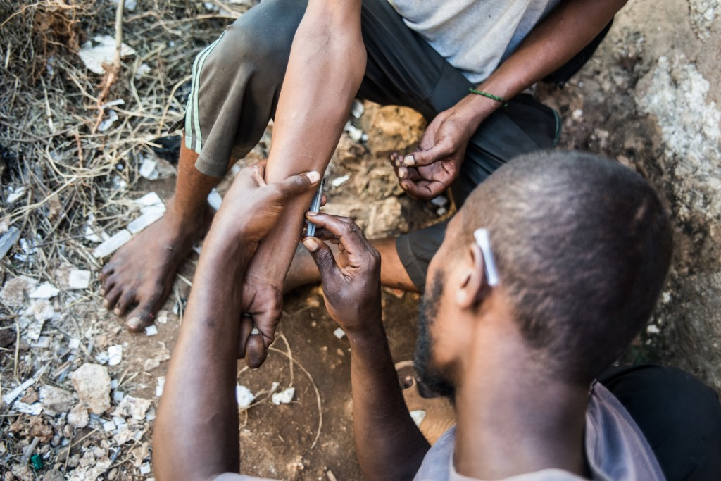 Ahmed Mohamed, right, known as 'the doctor' in this neighborhood, teaches Shee Omar how to shoot heroin safely. Photo by Mia Collis/PBS NewsHour