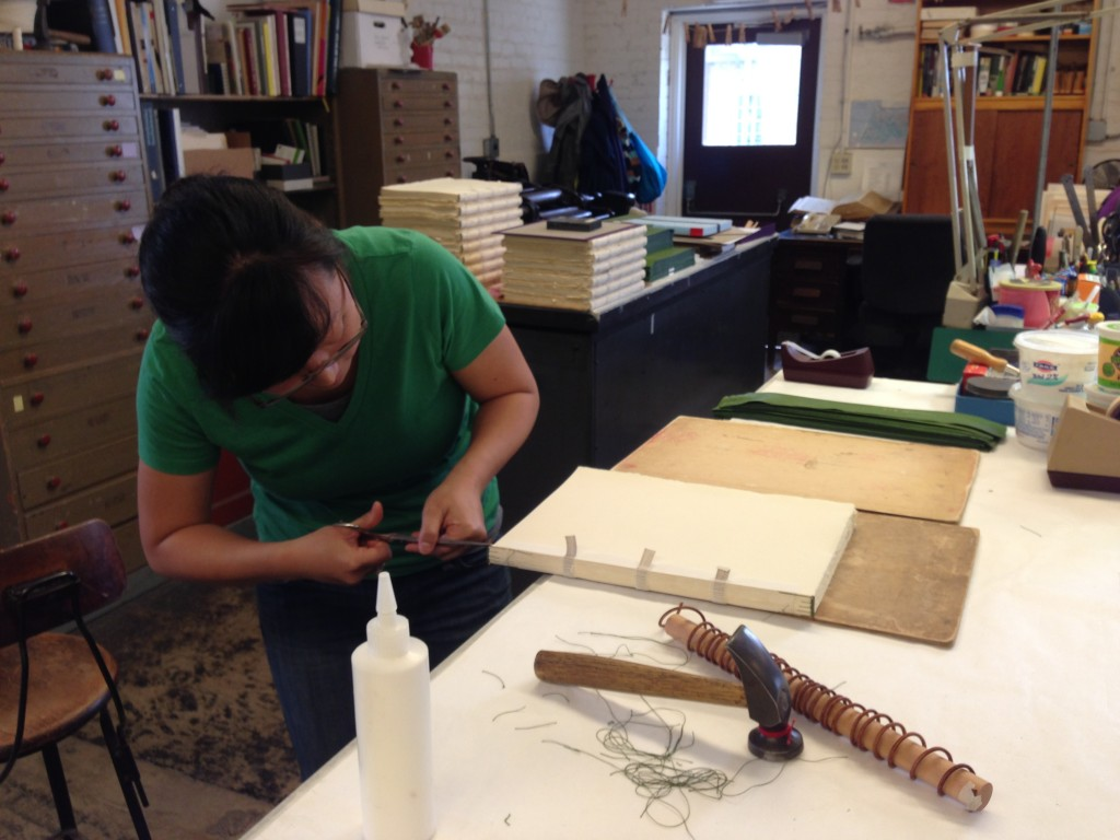"Arion bookbinder Rochelle Youk trims the handsewn binding of a nearly finished ""Leaves of Grass."" Drawings of grass made by Youk appear at the beginning and end of the book, as well as on the spine. Photo by Cat Wise/PBS NewsHour"